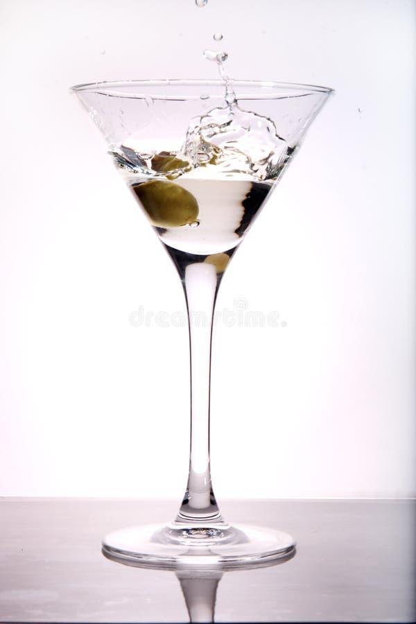 Azeitona que espirra em Martini foto de stock royalty free