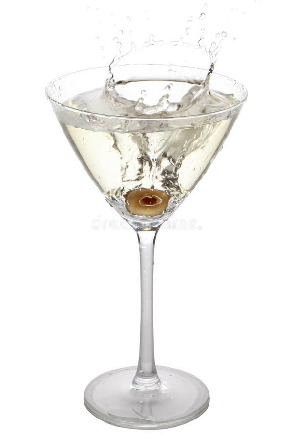 Azeitona que espirra em um vidro de cocktail imagens de stock