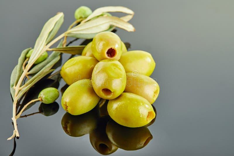 Azeitonas com um ramo de uma oliveira com os frutos que encontram-se em uma corrediça em um fundo cinzento foto de stock