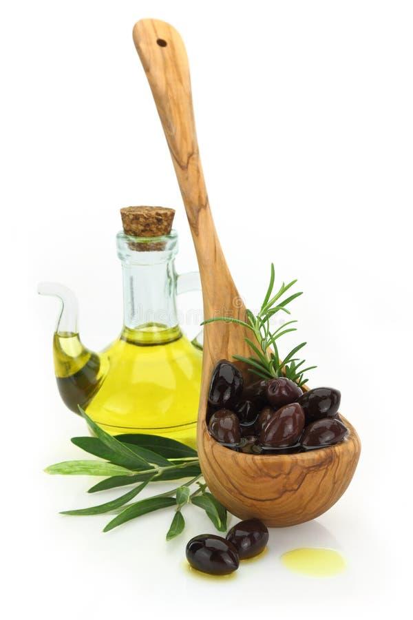 Azeitonas em uma colher de madeira e em uma garrafa do azeite virgem fotografia de stock