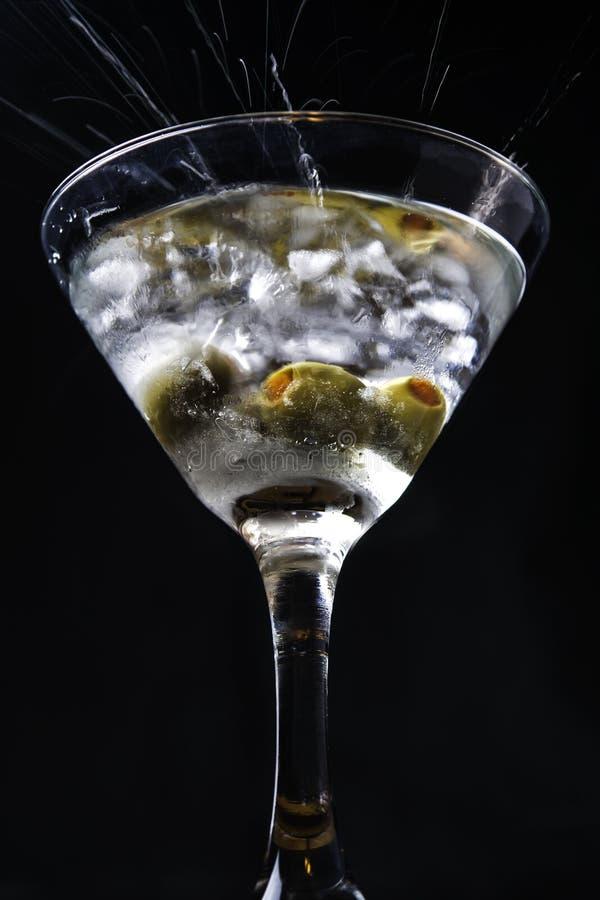 Azeitonas que espirram em um vidro de martini foto de stock royalty free