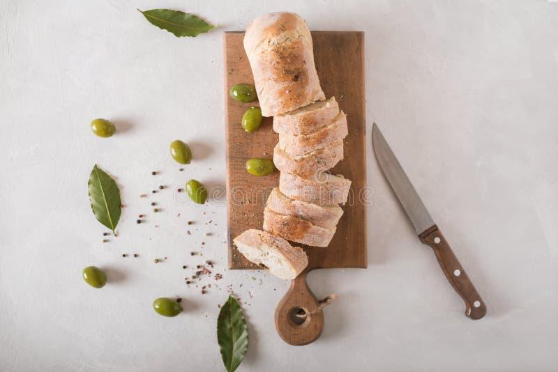 Azeitonas verdes, ciabatta cortado, em uma placa de madeira spice Ciabatta imagens de stock royalty free
