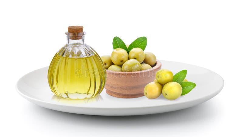 Azeitonas verdes e óleo na placa isolada em um fundo branco fotografia de stock