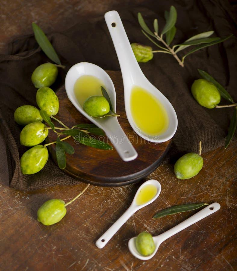 Azeitonas verdes, ramo de oliveira e azeite em uma placa de madeira escura foto de stock royalty free