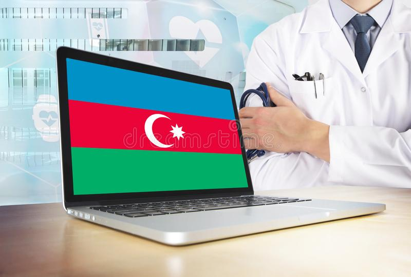 Azerbaijan healthcare system in tech theme. Azerbaijani flag on computer screen. Doctor standing with stethoscope in hospital. Cryptocurrency and Blockchain royalty free stock images