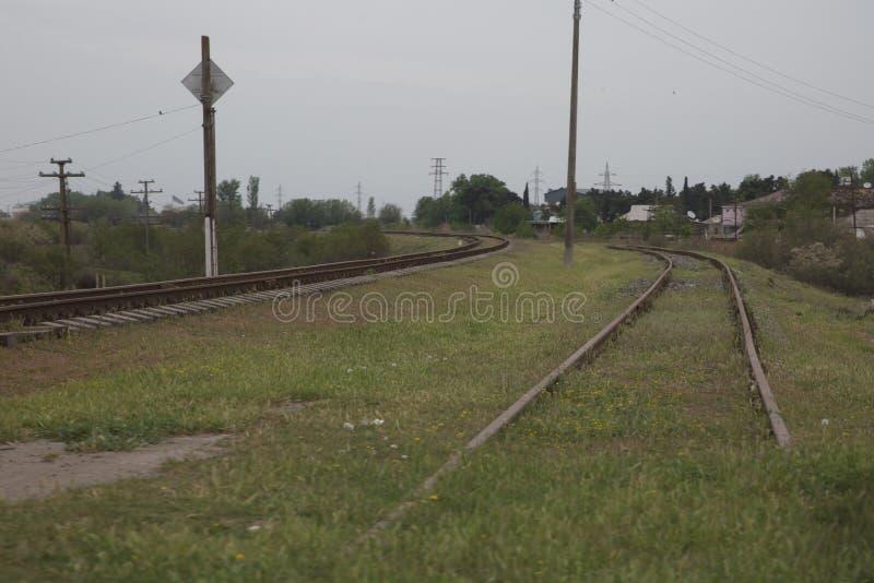 Azerbajdzjan järnväg in med himmel på grön bakgrund En järnväg vänder upprätt till och med vårgräsplanfältet I avståndet där arkivfoto