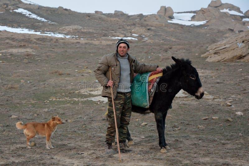 Azerbajdzjansk herde bredvid åsna med hunden arkivfoton