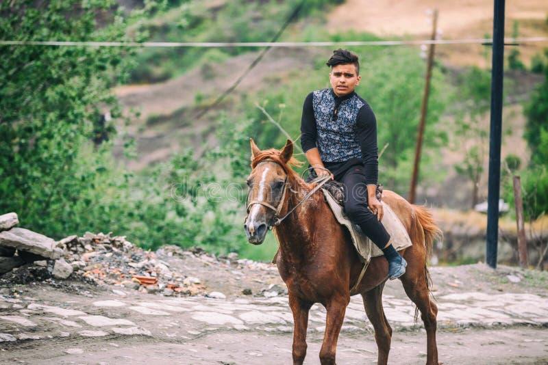 Azeri boy riding a horse in the Street on cobblestone Huseynov street, the main street of Lahic mountainous village of Azerbaijan, stock photos