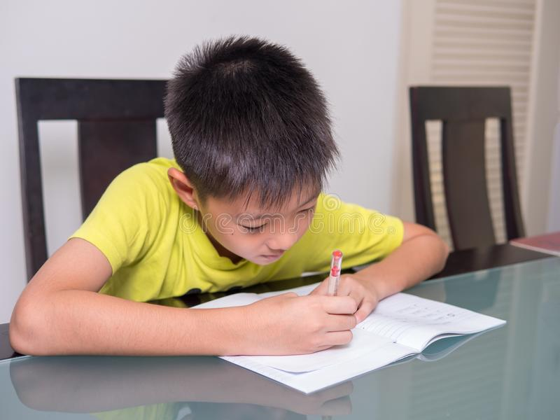 Azië weinig studentenjongen die en zijn thuiswerk bestuderen doen stock foto