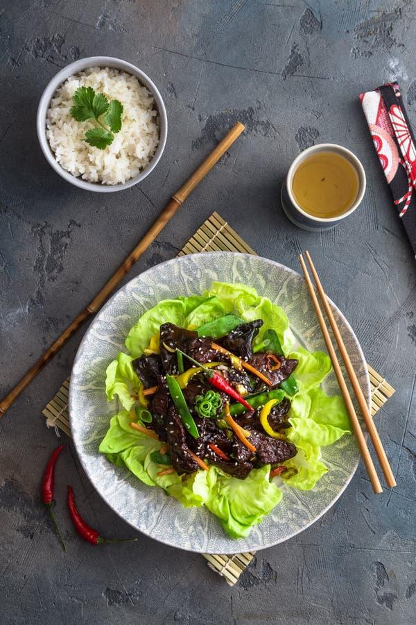 Aziaat beweegt gebraden kippenlever met kom rijst en groene thee stock afbeeldingen