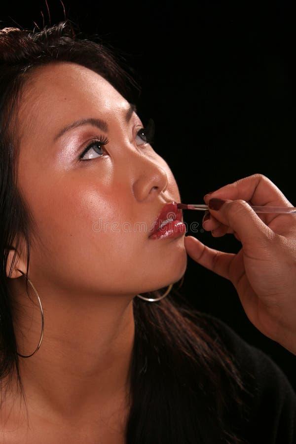 Aziaat die op make-up zet royalty-vrije stock foto