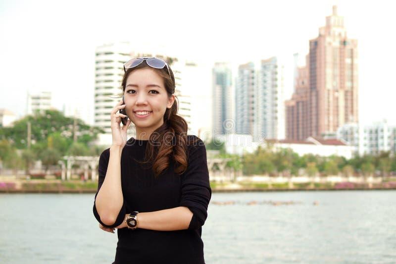 Aziaat die telefonisch met de bouw van achtergrond roept royalty-vrije stock afbeeldingen