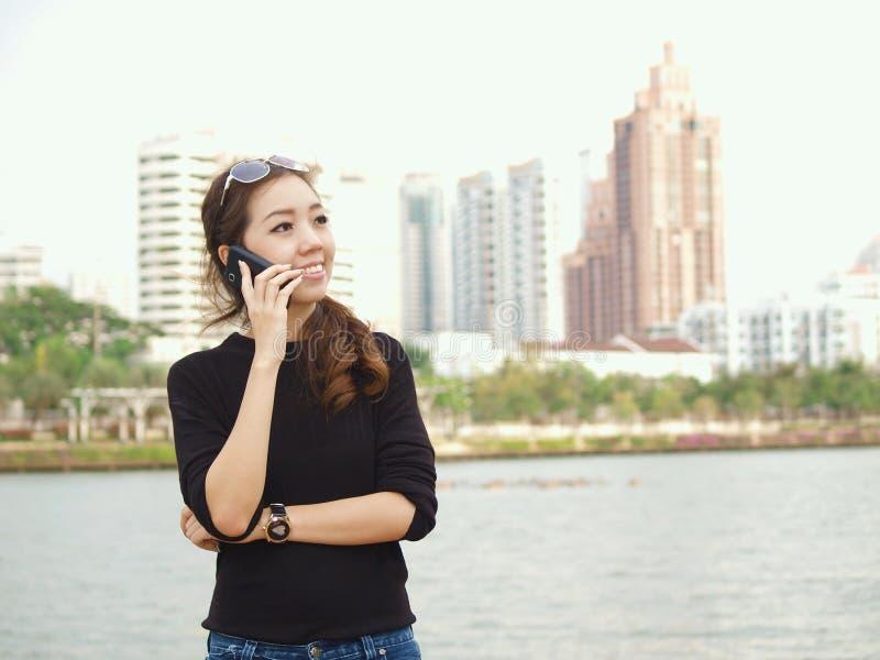 Aziaat die telefonisch met de bouw van achtergrond roept stock foto
