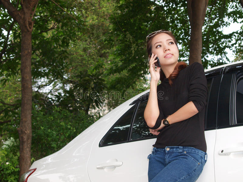 Aziaat die zich dichtbij auto bevindt en telefonisch roept royalty-vrije stock foto