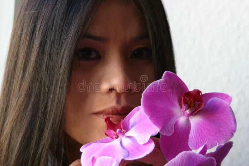 Aziaat met orchideeën royalty-vrije stock foto's