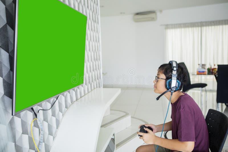 Aziaat preteen de videospelletjes van jongensspelen met een bedieningshendel royalty-vrije stock afbeeldingen