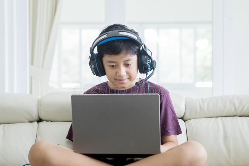 Aziaat preteen jongen gebruikend laptop en hoofdtelefoons royalty-vrije stock fotografie