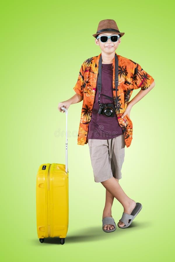 Aziaat preteen jongen houdt een bagage op studio stock afbeelding