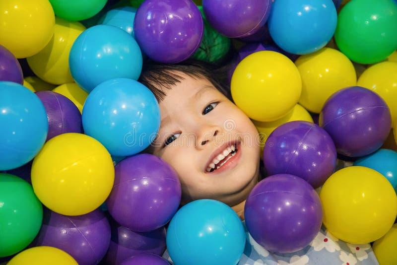Aziaat Weinig Chinees Meisje die met Kleurrijke Plastic Ballen spelen stock afbeeldingen