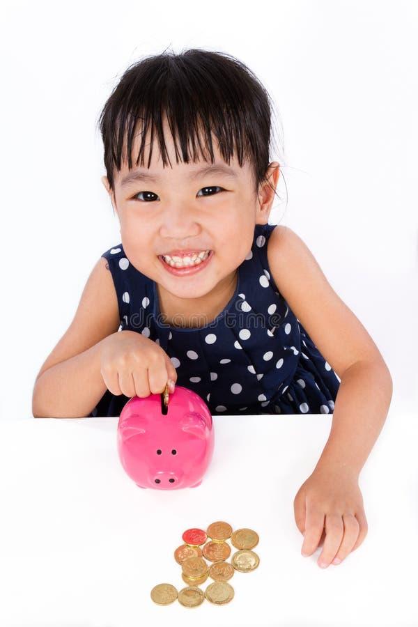 Aziaat Weinig Chinees Meisje die Muntstukken zetten in Spaarvarken stock afbeeldingen