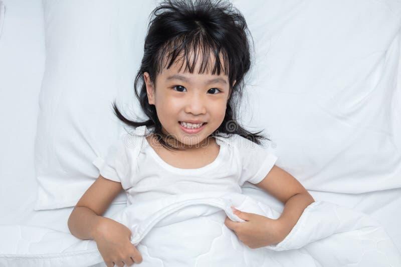 Aziaat weinig Chinees meisje die op het bed liggen royalty-vrije stock afbeeldingen