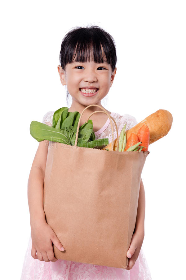 Aziaat weinig Chinese meisje dragende het winkelen zak met kruidenierswinkels stock fotografie