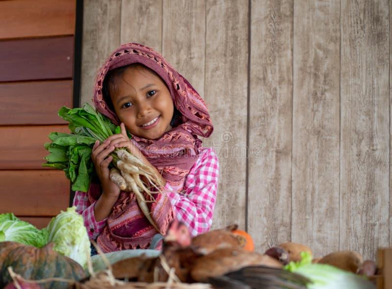Aziaat weinig jong meisje kijkt vooruit en glimlacht onder diverse types van groente houdt ook de radijs binnen achter kip op de  stock afbeeldingen