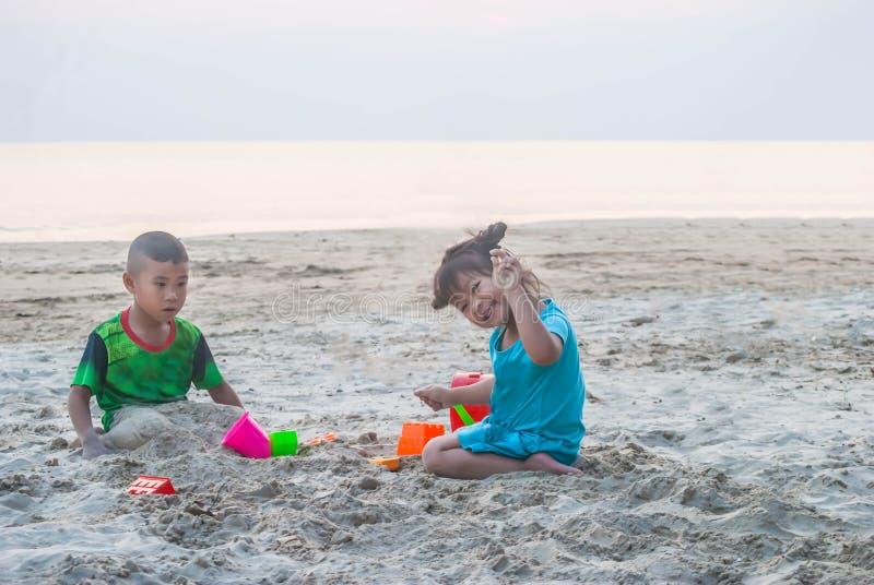 Aziaat weinig jongen en meisje speelt samen op zandige beac royalty-vrije stock afbeeldingen