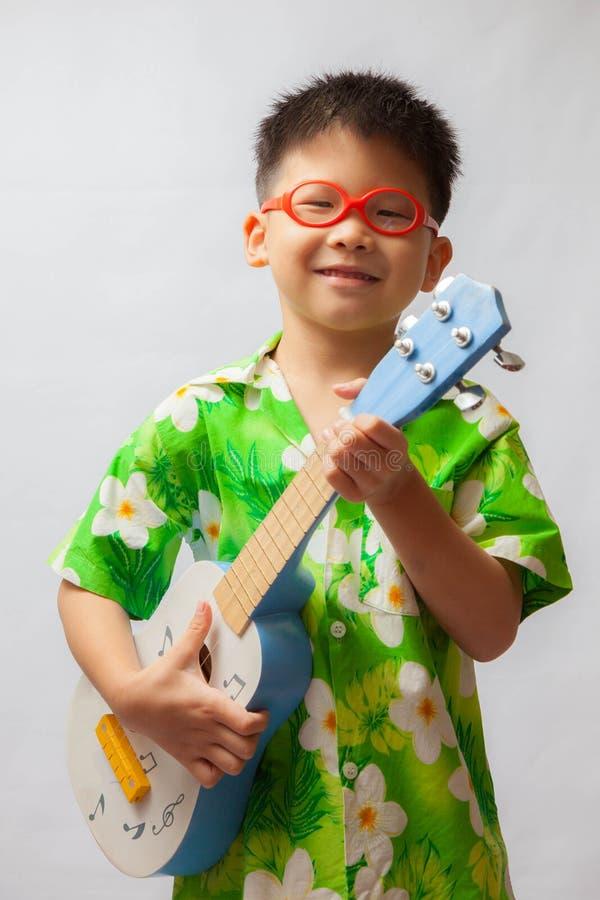 Aziaat weinig jongen het spelen ukelele stock afbeelding