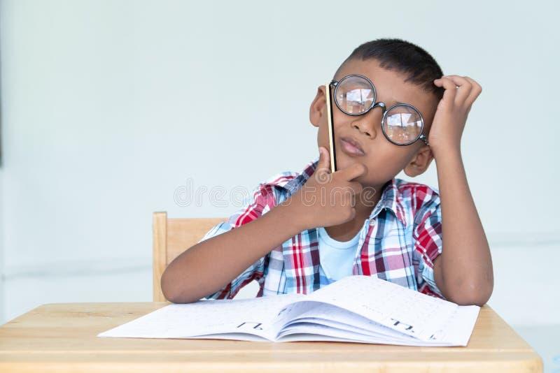 Aziaat weinig jongen schrijft thuiswerk stock foto