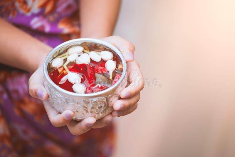 Aziaat weinig kindmeisje die een kleine kom voor het gieten op handen van bejaarden houden stock fotografie