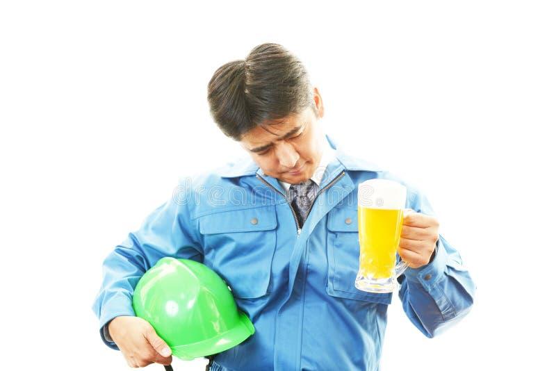 Aziatisch arbeider het drinken bier stock foto's