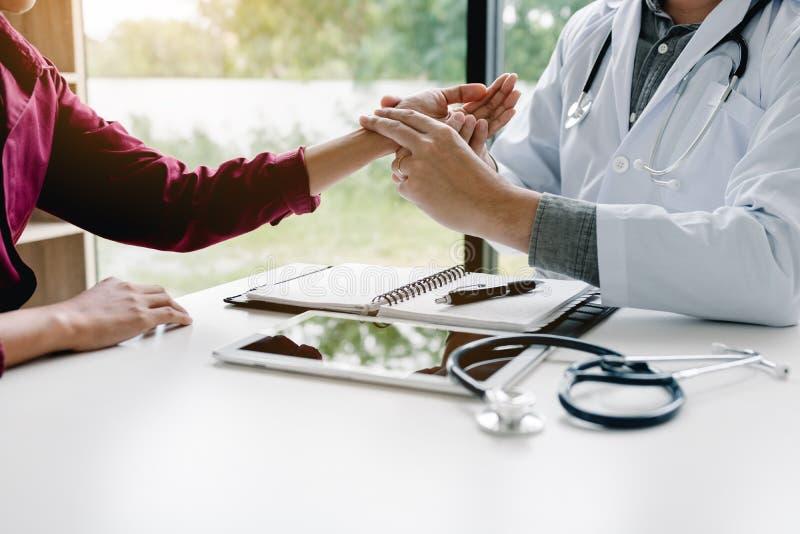 Aziatisch artsenmannetje met holdingshanden en arts die een geduldige impuls nemen bij kliniekruimte royalty-vrije stock foto