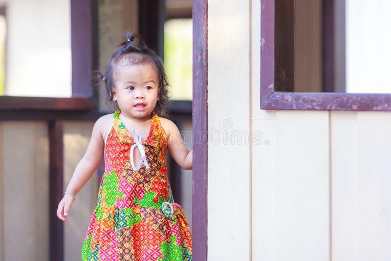 Aziatisch babymeisje achter de deur stock afbeelding