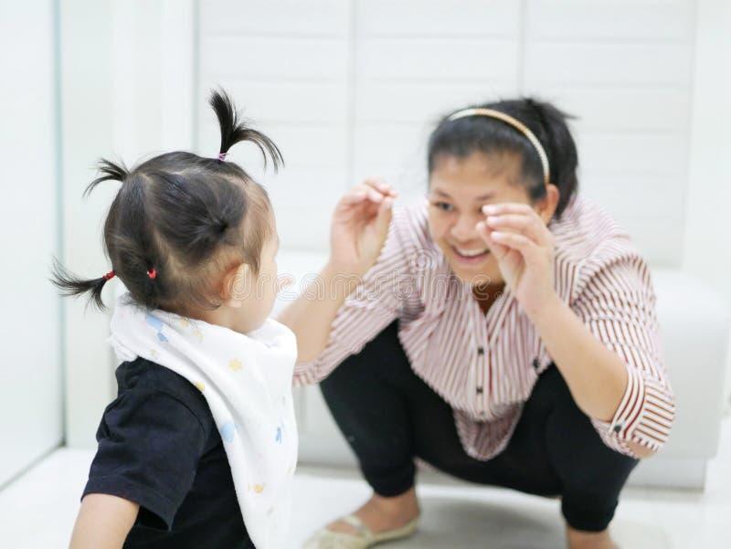 Aziatisch babymeisje die haar moeder bekijken die grappig gebaar maken om haar onderhouden te houden, terwijl het wachten om de a royalty-vrije stock foto's