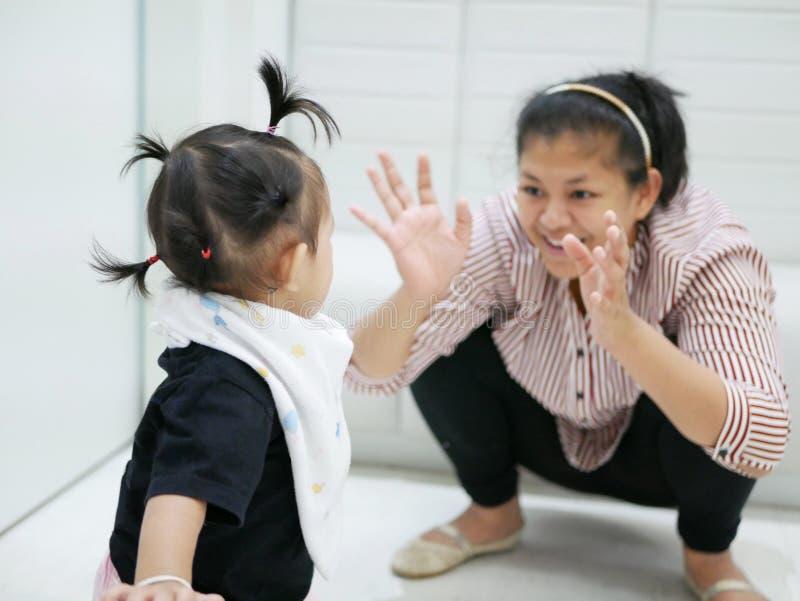 Aziatisch babymeisje die haar moeder bekijken die grappig gebaar maken om haar onderhouden te houden, terwijl het wachten om de a stock foto