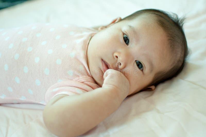 Aziatisch babymeisje die op bed leggen stock afbeeldingen