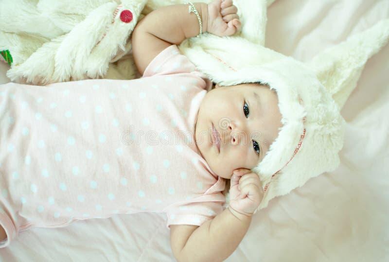 Aziatisch babymeisje die op bed leggen stock foto's