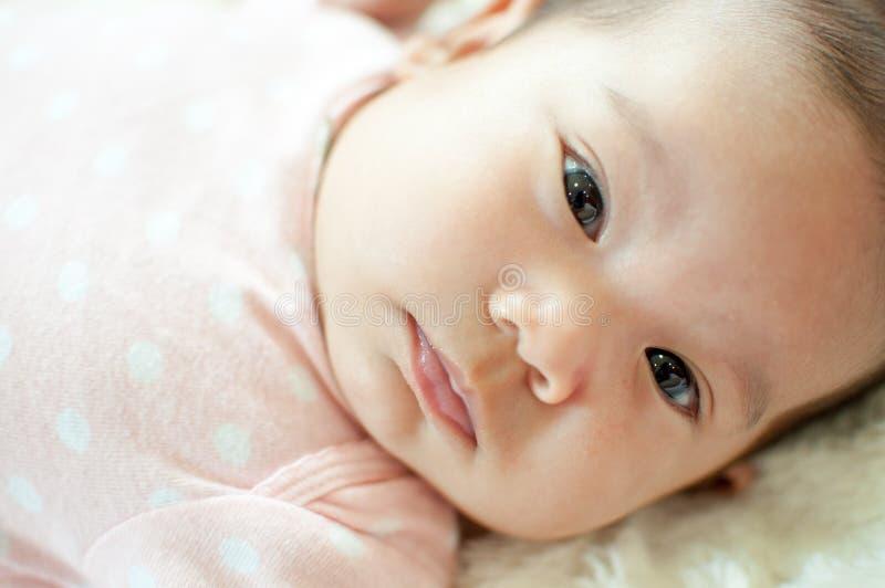 Aziatisch babymeisje die op bed leggen royalty-vrije stock afbeelding