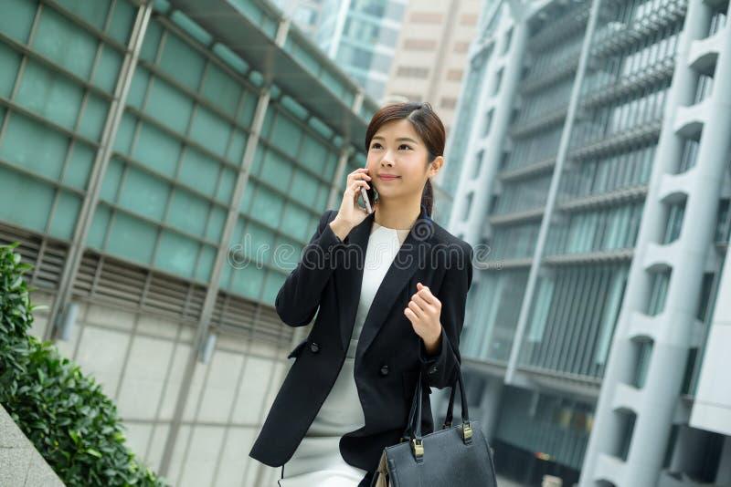 Aziatisch bedrijfsvrouwenpraatje op mobiele telefoon stock foto