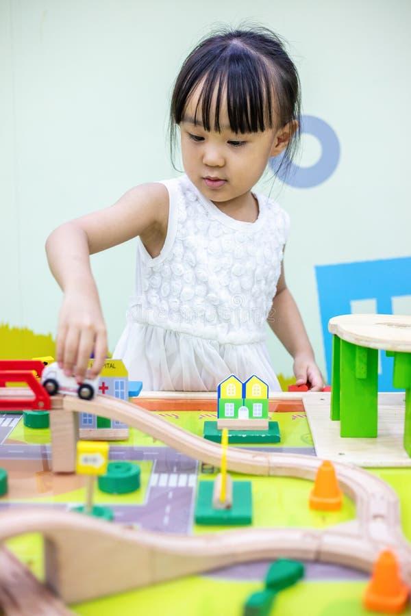 Aziatisch Chinees meisje die houten stuk speelgoed trein spelen royalty-vrije stock afbeelding