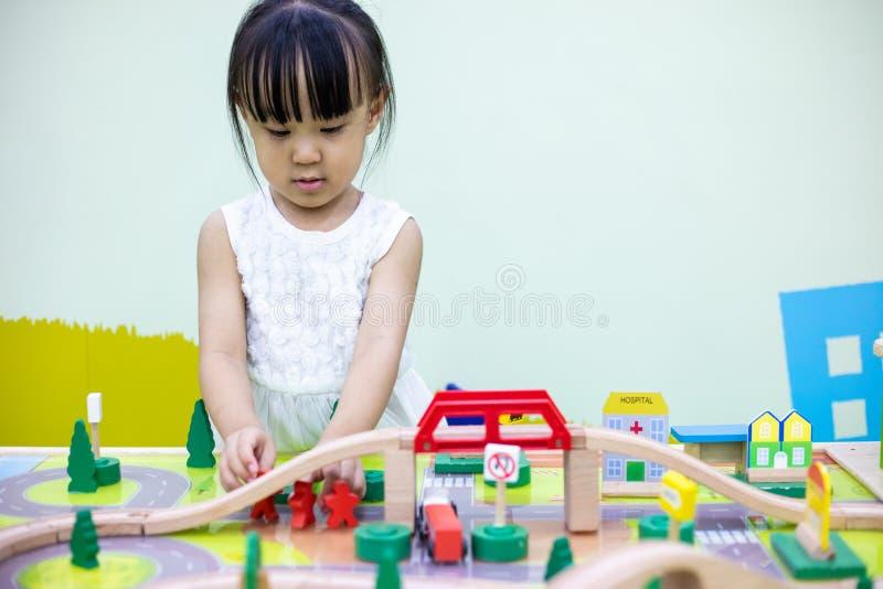 Aziatisch Chinees meisje die houten stuk speelgoed trein spelen stock afbeeldingen