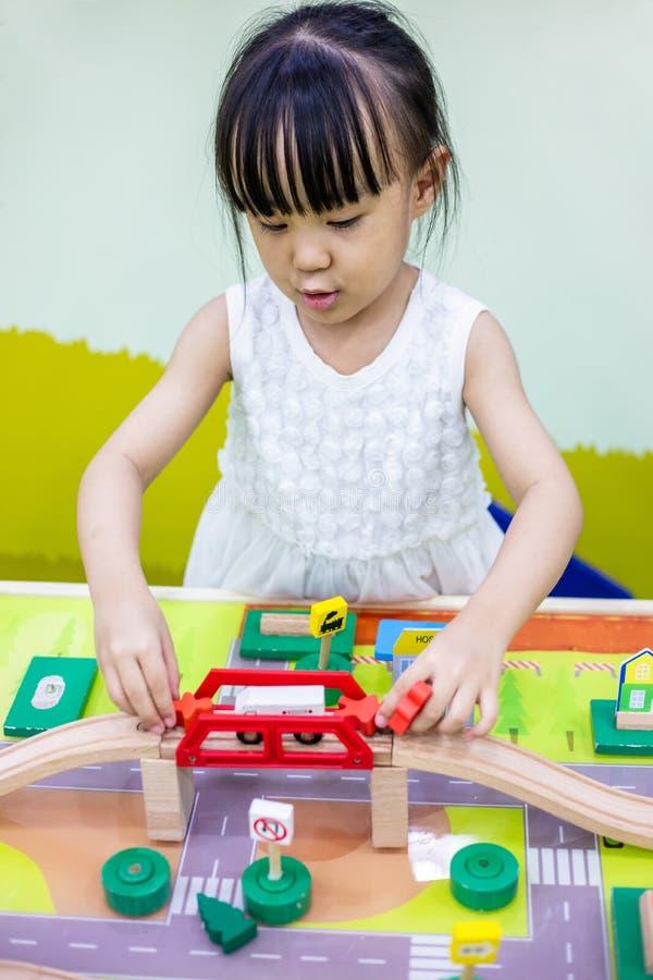 Aziatisch Chinees meisje die houten stuk speelgoed trein spelen stock foto's