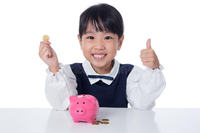Aziatisch Chinees meisje die muntstukken zetten in spaarvarken royalty-vrije stock afbeelding