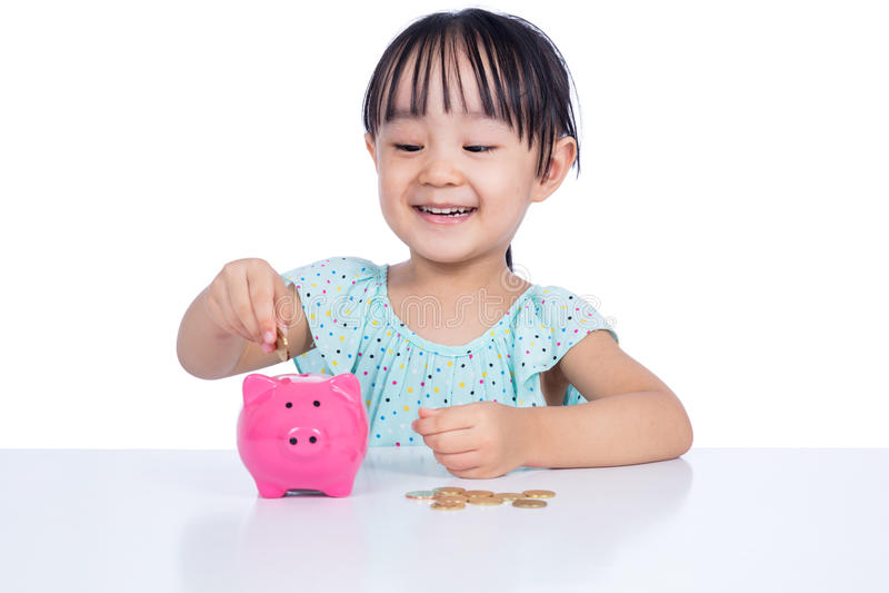 Aziatisch Chinees meisje die muntstukken zetten in spaarvarken stock fotografie