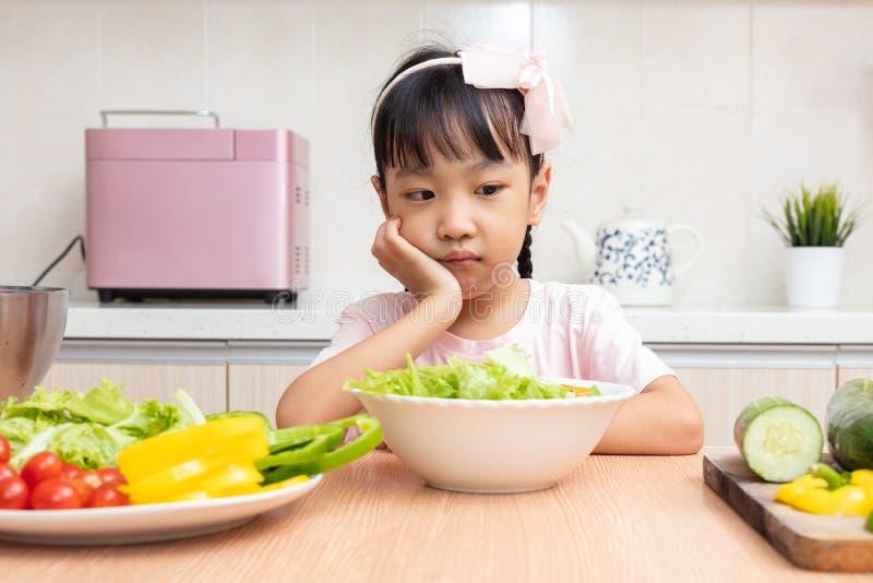 Aziatisch Chinees meisje die salade in de keuken eten royalty-vrije stock foto