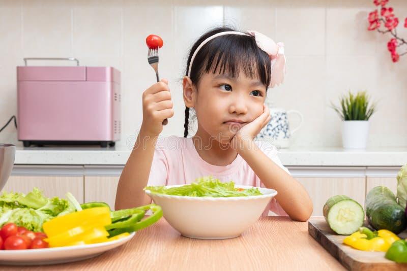 Aziatisch Chinees meisje die salade in de keuken eten royalty-vrije stock afbeeldingen