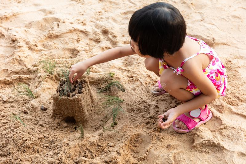 Aziatisch Chinees meisje het spelen zand bij strand stock afbeelding