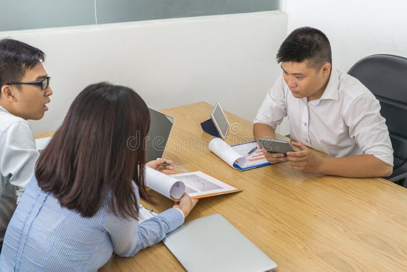 Aziatisch commercieel team die de financiële statistieken analyseren stock afbeeldingen