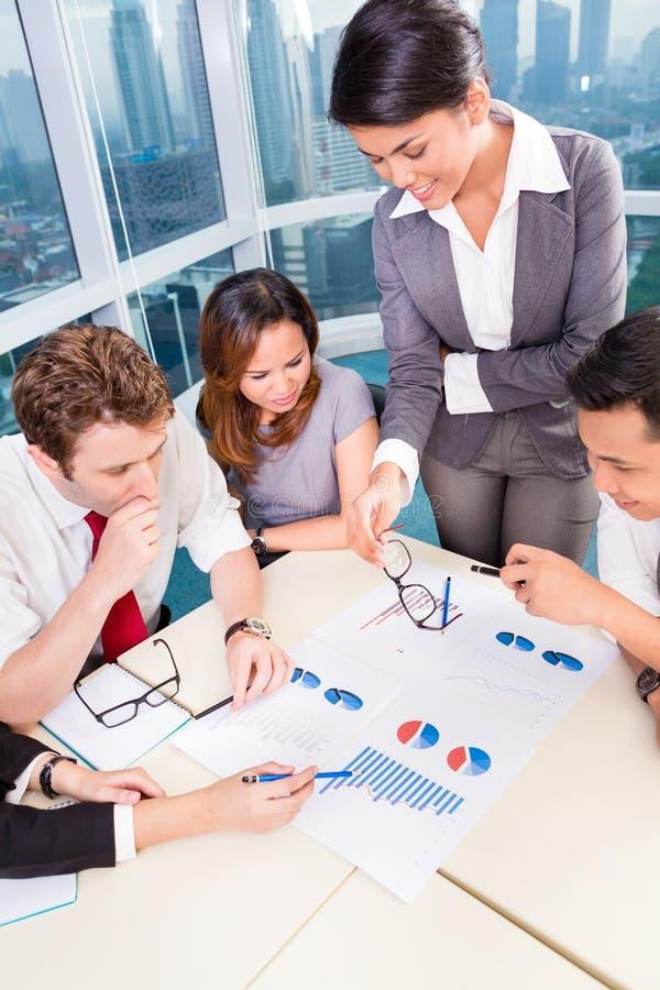 Aziatisch Commercieel team die grafieken bespreken royalty-vrije stock afbeeldingen